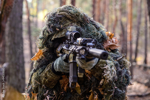 Canvas Print Sniper aiming from his rifle in forest/Portrait of sniper in the woods, which  a