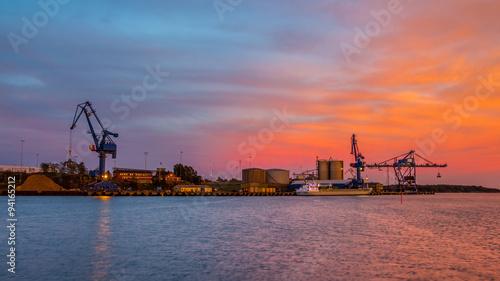 Fotografia Massive blue cranes unload cargo in a seaport during sunset