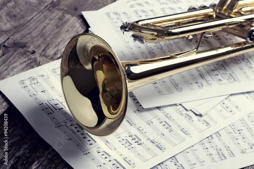 Obraz na plátně Trumpet and sheet music on old wooden table. Vintage style.