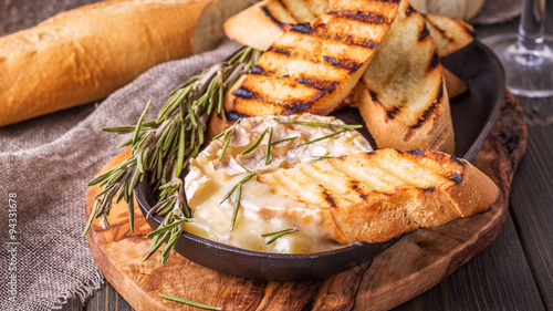 Homemade baked camembert with toasted bread and rosemary.
