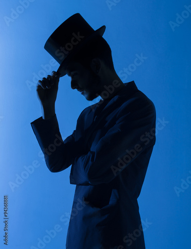 Billede på lærred Silueta de un mago con chistera en azul