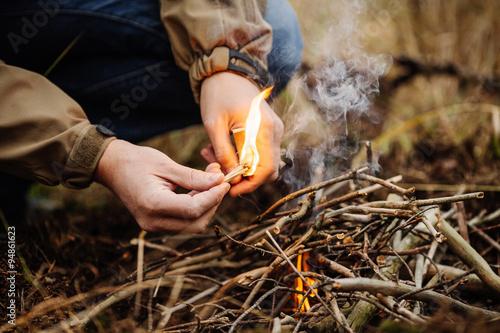 Obraz na płótnie young man kindles a fire in summer wood
