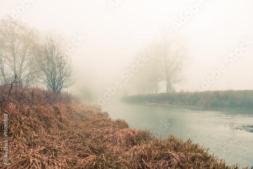 Stampa su Tela foggy fall riverside at fall morning