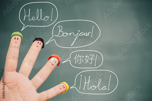 Photo Four smiley fingers on a blackboard saying hello in English, French, Chinese and Spanish