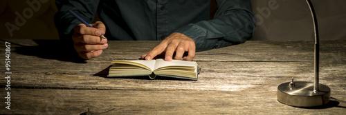 Foto Mann, der an seinem Schreibtisch sitzen, um eine Notiz in seinem Notizblock mach