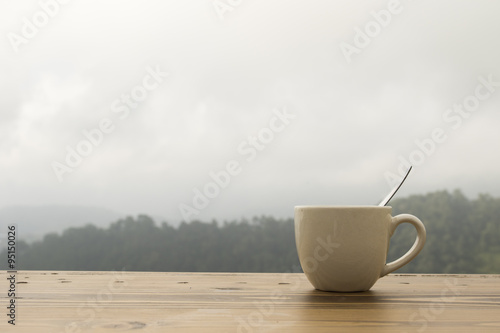 coffee cup on wooden table with natural moutain background
