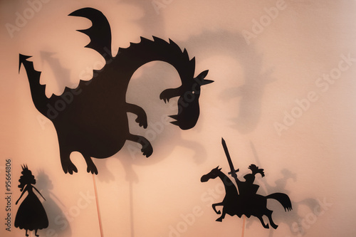 Fototapeta premium Shadow Puppets of Dragon, Princess and Knight z jasnym świecącym ekranem teatru cieni w tle.