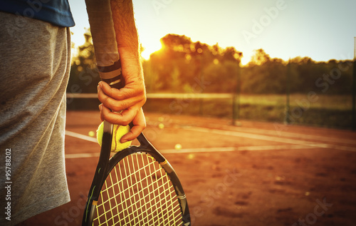Man holding tennis racket/Close up of man holding tennis racket on clay court. In his hand is tennis ball. On court is sunset.