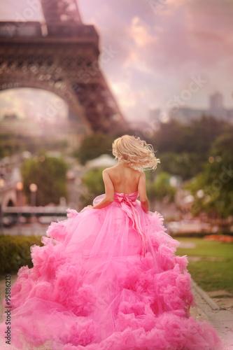 Fotografie, Obraz beautiful girl in a pink dress runs on the background Eiffel Tower in Paris