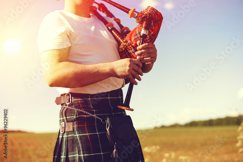 Stampa su Tela young man playing pipes in national uniform on green summer outdoors copy space