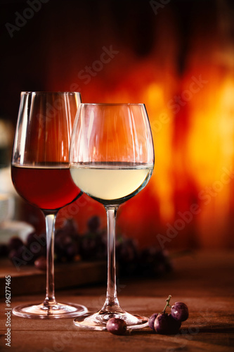 Red and white wine in front of a blazing fire #96277465