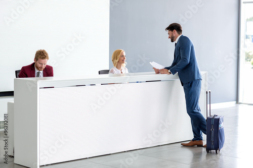 Carta da parati Businessman flirting at reception with female receptionist