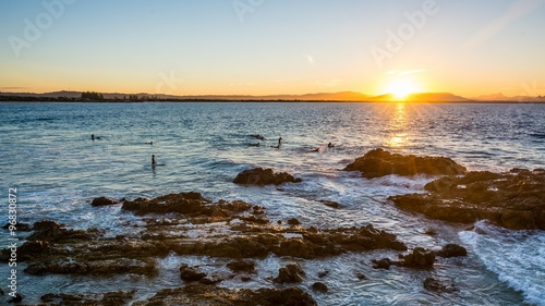 Canvas Print Surfer on waves in the sunset at byron bay
