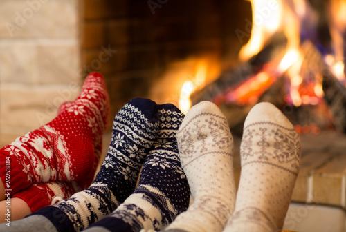 Canvas Print Feet in wool socks near fireplace in winter time