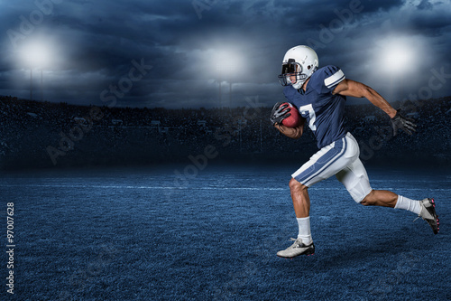Canvas Print American Football Player Running for a touchdown in a large outdoor professional