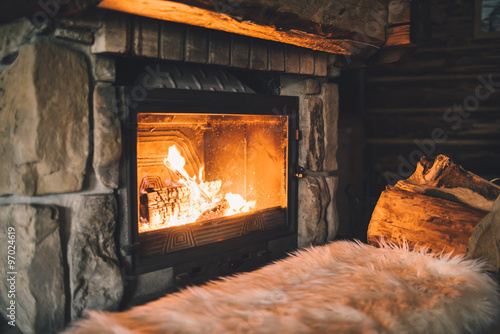 Stampa su Tela Warm cozy fireplace with real wood burning in it