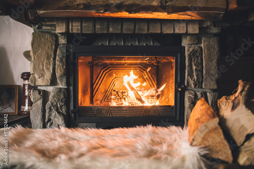 Leinwand Poster Warm cozy fireplace with real wood burning in it