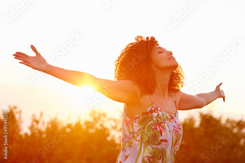 Fototapeta Woman outstretched arms in an expression of freedom with sunflar