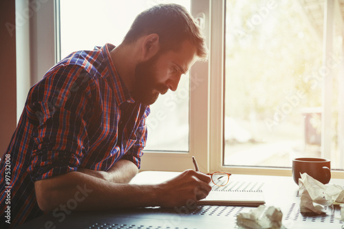 bearded man writing in notebook with pen and paper balls