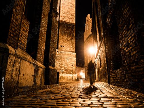 Obraz na plátne Illuminated cobbled street in old city by night