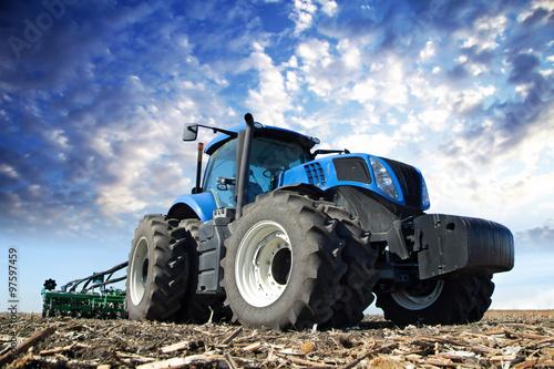Błękitny ciągnik pracuje na gospodarstwie rolnym Fototapeta