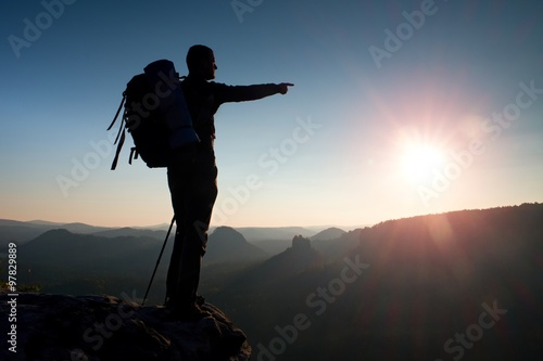 Fotografie, Obraz Sharp silhouette of a tall man on the top of the mountain with sun in the frame