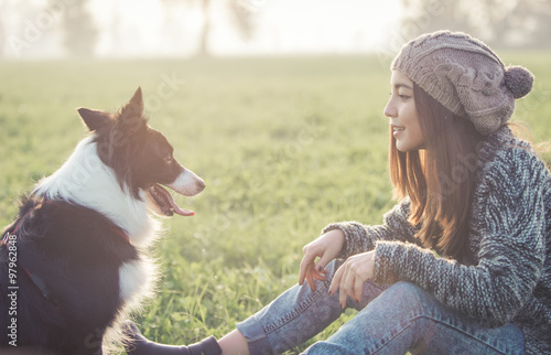 Tableau sur Toile Young woman playing with her border collie dog