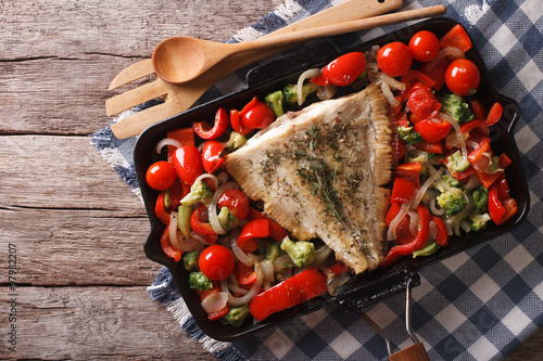 Valokuva flounder with vegetables on a frying pan. Horizontal top view