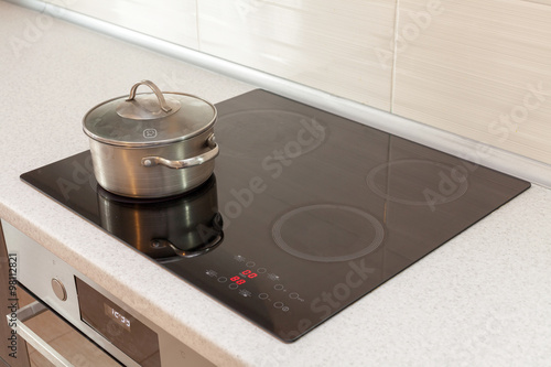 Slika na platnu Metal steel saucepan in modern kitchen with induction stove