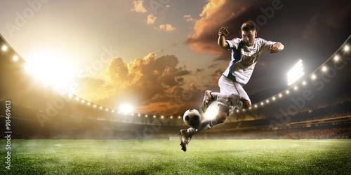 Fototapeta premium Gracz piłki nożnej w akci na zmierzchu stadium panoramy tle