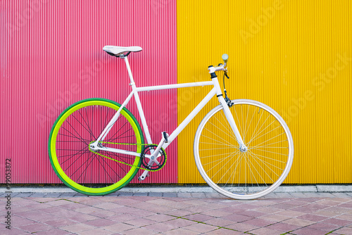 City bicycle fixed gear on yellow and red wall.
