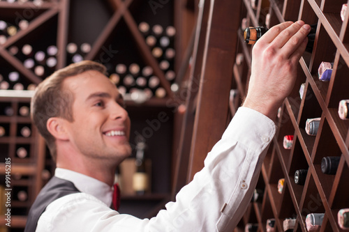 Canvas Print Handsome young worker is choosing an elegant drink