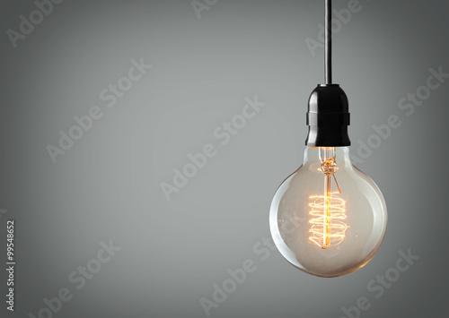 Vintage hanging light bulb over gray background Fototapet