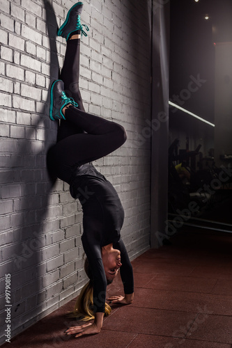 Fotografie, Tablou Attractive woman do handstands in the gym