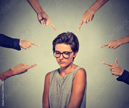 Fotografia Sad embarrassed woman in glasses looking down many fingers pointing at her