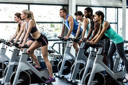 Fototapeta Fit people working out at spinning class