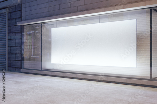 Fotografia Large blank banner in a shop window at night, mock up