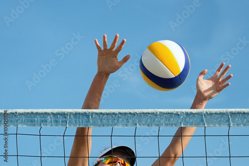 Beach volley ball player jumps on the net and tries to blocks the ball