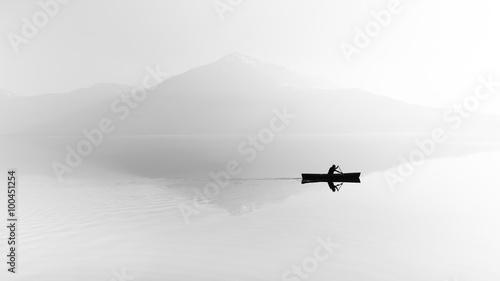 Fototapeta premium Mgła nad jeziorem. Sylwetka gór w tle. Mężczyzna unosi się w łodzi z wiosłem. Czarny i biały