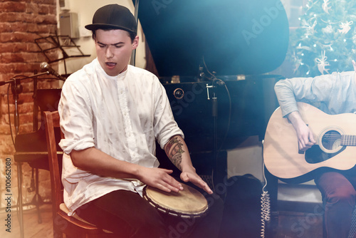 Fototapeta stylish percussionist playing on leather drum on a concert, hand