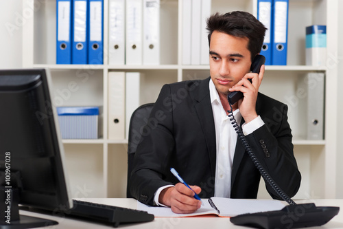Foto Sympathischer Mitarbeiter berät am Telefon