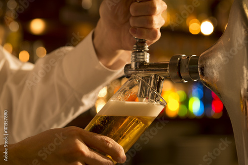 Foto The bartender is pouring draft beer
