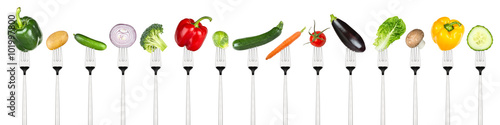 Fototapete row of tasty vegetables on forks isolated on white background