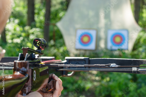 Fotografia Man aiming crossbow at targets in summer forest