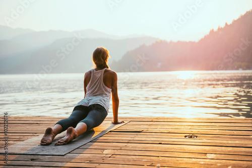 Yoga sun salute. Young woman doing yoga by the lake at sunset Fototapeta