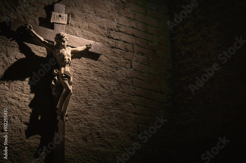 Leinwand Poster Dark artistic cross on a shaded rough textured brick wall