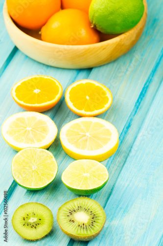 Ripe kiwi, lime, lemon, orange fruit on wooden vintage background. Healthy vegetarian food. Recipe, menu, mock up, cooking.