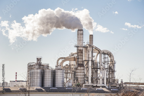 Chimneys and silos of a factory. Fototapet