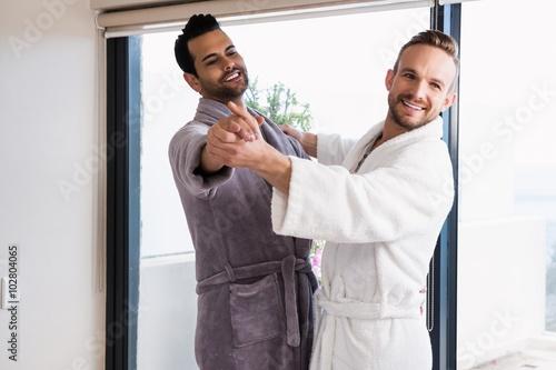 Happy gay couple dancing waltz in bathrobe Fototapeta