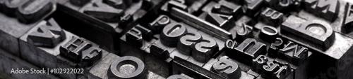 Rodzaje druków metalowych. Tło z wielu historycznych liter w czerni i bieli z białym tłem.